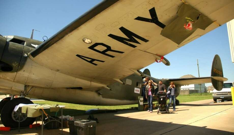 Visitors disembark a C-60A Lodestar on Saturday. The twin-engine plane has been restored by the West Houston Squadron to its paratroop transport configuration. Photo: Rusty Graham