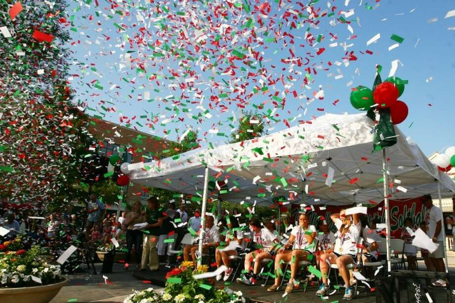 The Woodlands High School softball team smiles behind a wall of confetti during a parade on Market Street to honor their state championship.