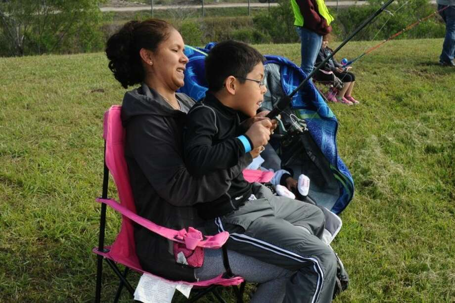 Ricky Aquines and his mother Roxanne Aquines reel in a catfish during the Deer Park kid fish event benefiting the Deer Park High School FFA Saturday, Apr. 21.