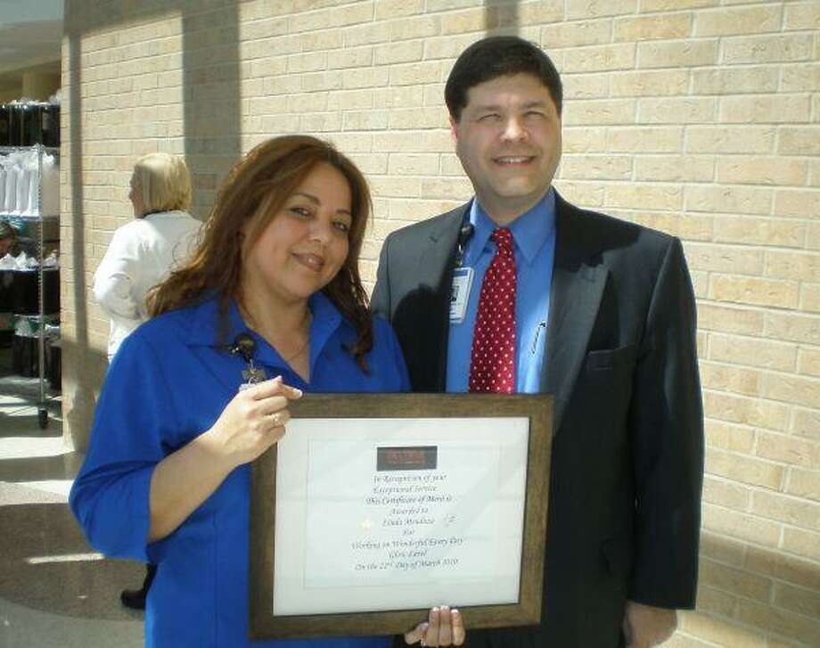 Memorial Hermann Northeast Hospital CEO Louis Smith congratulates Linda Mendoza, a hospital employee who works in the Patient Access Department, as one of Northeast's most patient-pleasing employees. Mendoza and 137 other Northeast employees were honored recently for employees who received three or more patient compliments in February.