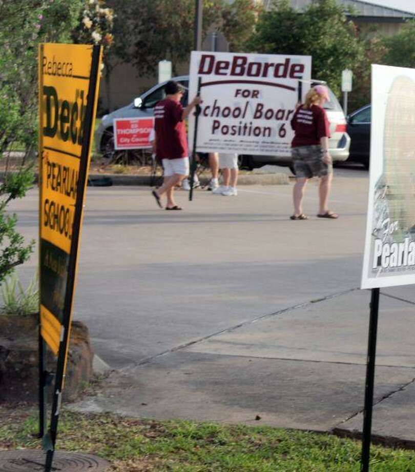 Supporters of PISD Trustee Candidate Rusty DeBorde begin taking down election campaign signs after polls closed on Saturday.