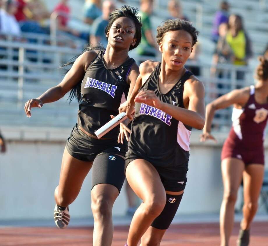 Sharica Flournoy (left) hands the baton off to Kyndall McKinney on the third leg of the 4x200 relay at the District 18-4A Track and Field Championships, held April 11 at Turner Stadium in Humble. Photo: Photo By Stephen Whitfield