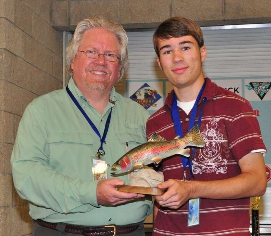 Wildlife Forever's Doug Grann presented Brady King with the trophy for the Seth Thomas Spradlin Best of Show award. The rainbow trout was Seth Spradlin's favorite fish. Photo: Submitted Photo