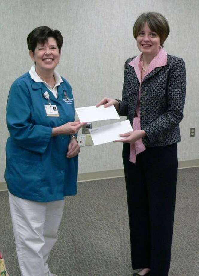 Susan Muller, left, of the Houston Northwest Medical Center Hospital Auxiliary presents two checks of $1,000 each to Northwest Assistance Ministries' vice president of fund development, Maria Magee. One gift was for NAM's general fund and the other was for NAM's Family Violence Center.