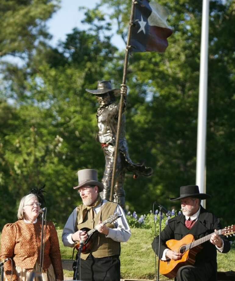 A band in period clothing plays music beneath the Texan statue at the Lone Star Flag Park during the kickoff for the Texas Legacy Festival on Friday in Conroe.