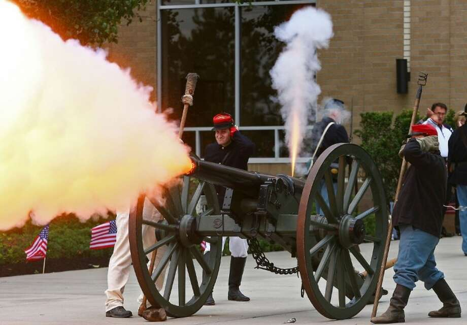 """The 11th Texas Light Artillery fires a cannon at the conclusion of """"God Belss America"""" during a Celebrate America service Sunday at Mims Baptist Church in Conroe."""