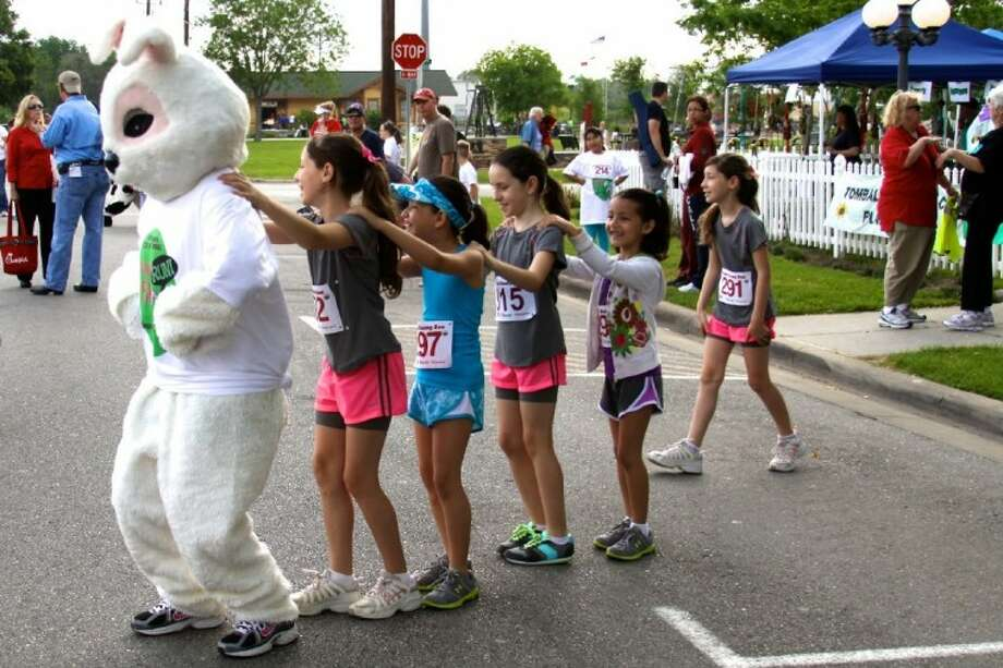 The Bunny leads a group of children in a Bunny Hop parade before the 4th Annual Bunny Run Saturday.
