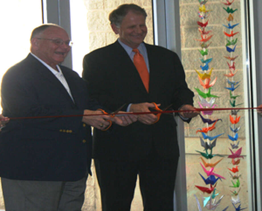 Chairman of the Board for the Pearl Fincher Museum of Fine Arts Calvin Cobb and Congressman Ted Poe (R-Dist. 2) recognize the completion of the facility with a ribbon cutting.
