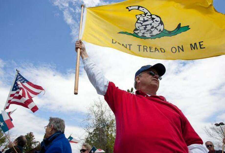 North Houston Tea Party member John Wertz waves a large Gasden flag as the group protested the Obama administration's health care reform bill near The Woodlands Mall on Sunday afternoon. Wertz cited his son, currently serving at a forward operating base in Afghanistan, as his inspiration to participate in the movement. / The Courier