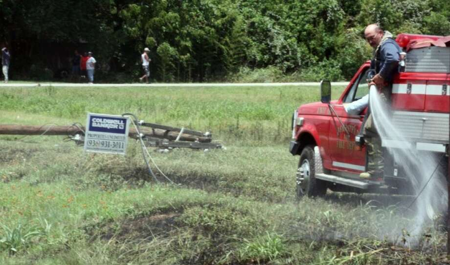 Hempstead firefighter Jimmy Orzac sprays down a hotspot Monday in a field off FM 1488. A hit-and-run driver knocked down two utility poles which sparked a small fire.