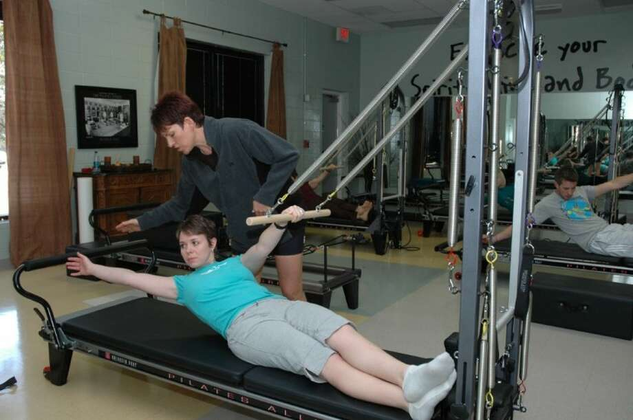 Shellee Eudy, Certified Pilates Reformer Instructor at the YMCA working with Michelle Hill on the reformer.