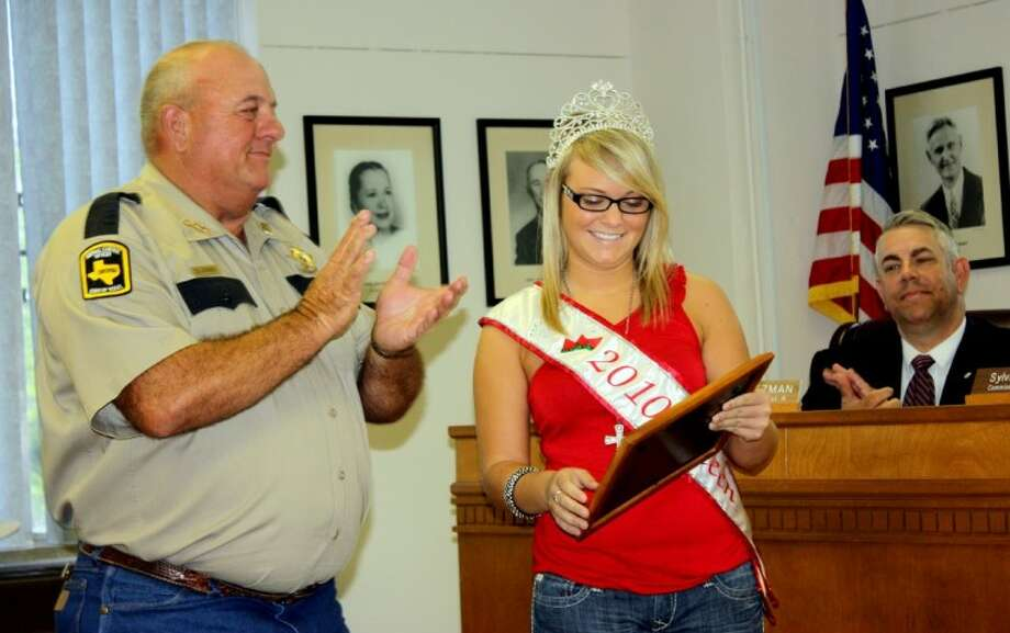 Faylin Riemer, the 2010 Hempstead Watermelon Queen, is awarded a plaque by Waller County Animal Control Officer Don Jones in recognition of her efforts to collect donations of food for dogs, cats and horses. The award was given at Tuesday's meeting of the Waller County Commissioners Court.