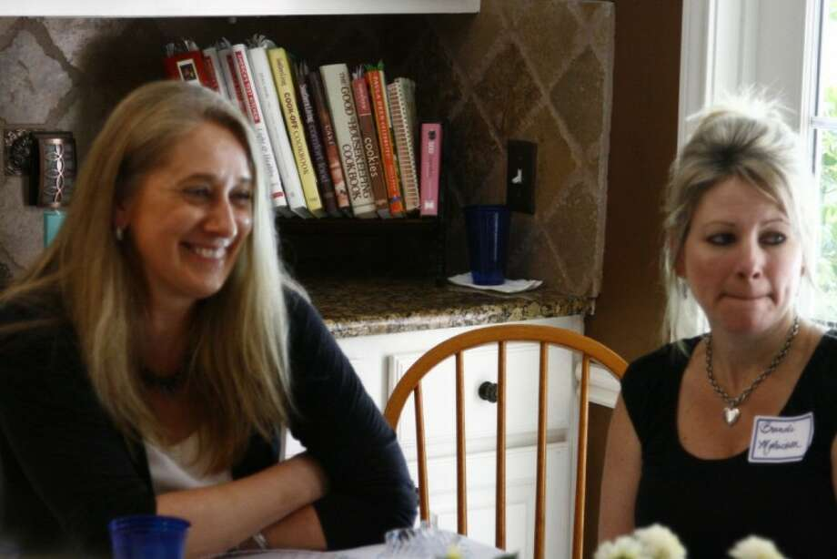 Julie Traut, left, shares a laugh with friends and fellow PTA members at a going-away party in her honor April 26.