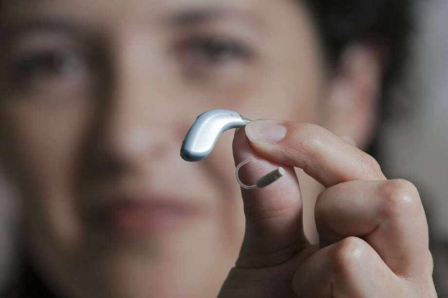 Hearing Specialist Mayra Takenaga holds up a hearing aid at Clarity Hearing in The Woodlands. Photo: Karl Anderson