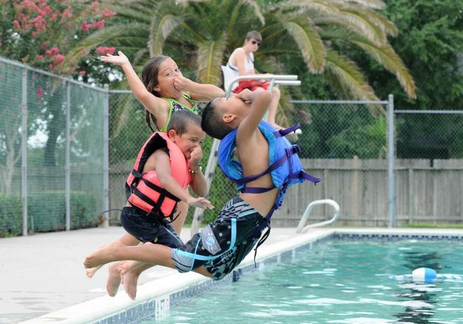 Lifeguard Kyle Thompson watches as left to right, Alexis Sullivan, Andrew Sullivan and Kadence Nguyen jump into the Brittany Bay community pool in League City.