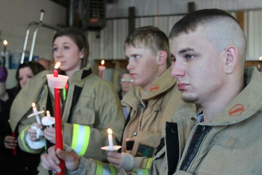 "Chase Franklin, Logan Holston and Rachel Arnold of Tarkington Volunteer Fire Department (TVFD) choked back their emotions and tears at a candlelight vigil in honor of Marshall ""Mow"" Ward, the 20-month-old son of TVFD firefighters, Jason and Leah Ward. Marshall was killed on April 17 at his home in Tarkington. Photo: VANESA BRASHIER"