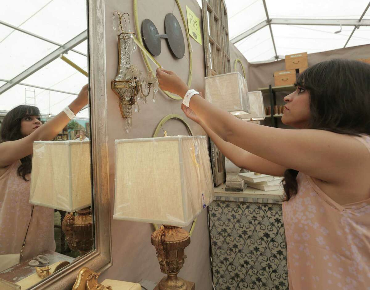 Amitha Verma, a Houston interior designer who owns Village Antiques, measures a sconce for a design client while antique shopping in Round Top.