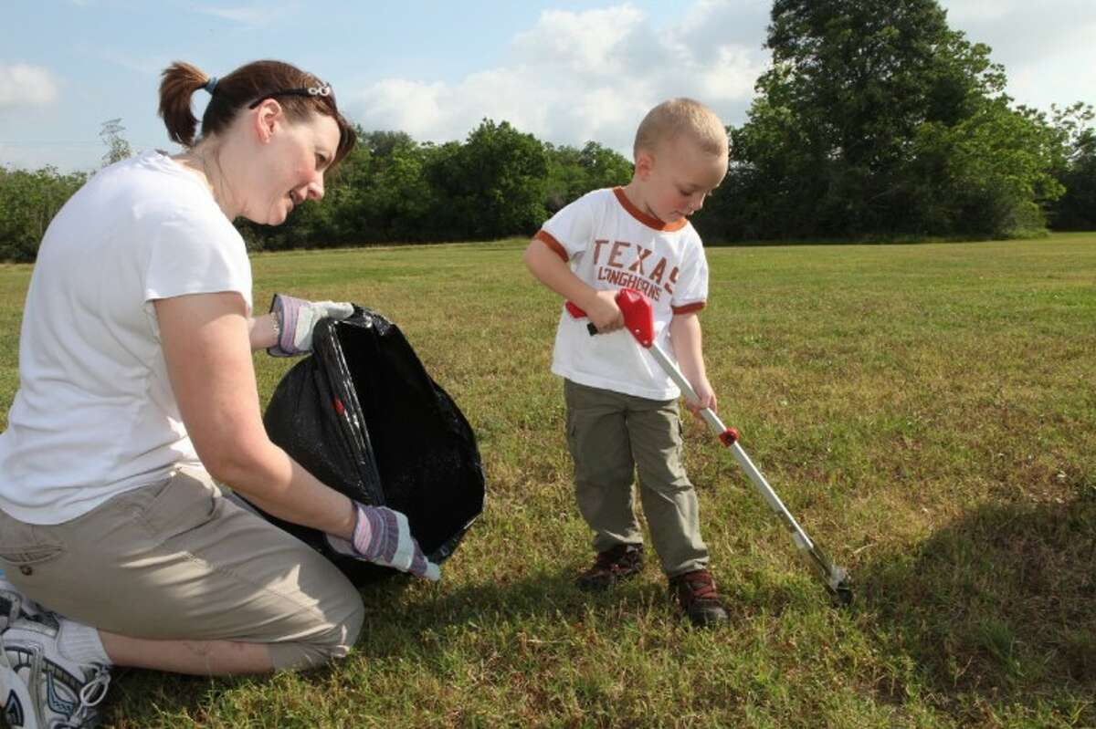 Cole Bradley, 3, and his mother Tami Bradley of Missouri City, pick up trash during the Great American Cleanup 2012 at Buffalo Run Park in Missouri City.