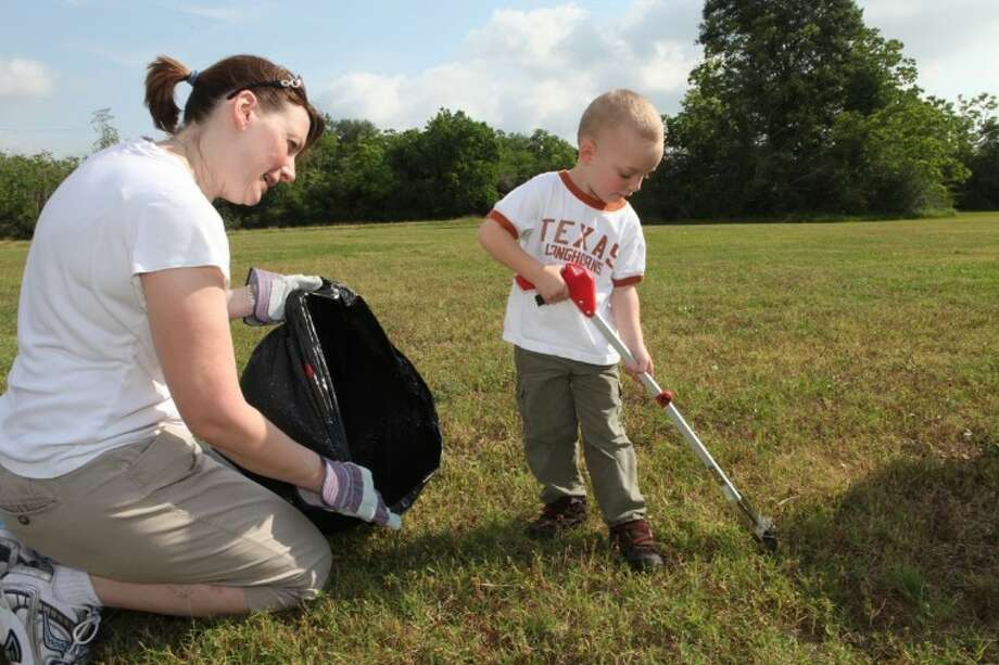 Cole Bradley, 3, and his mother Tami Bradley of Missouri City, pick up trash during the Great American Cleanup 2012 at Buffalo Run Park in Missouri City. Photo: Photo By Alan Warren