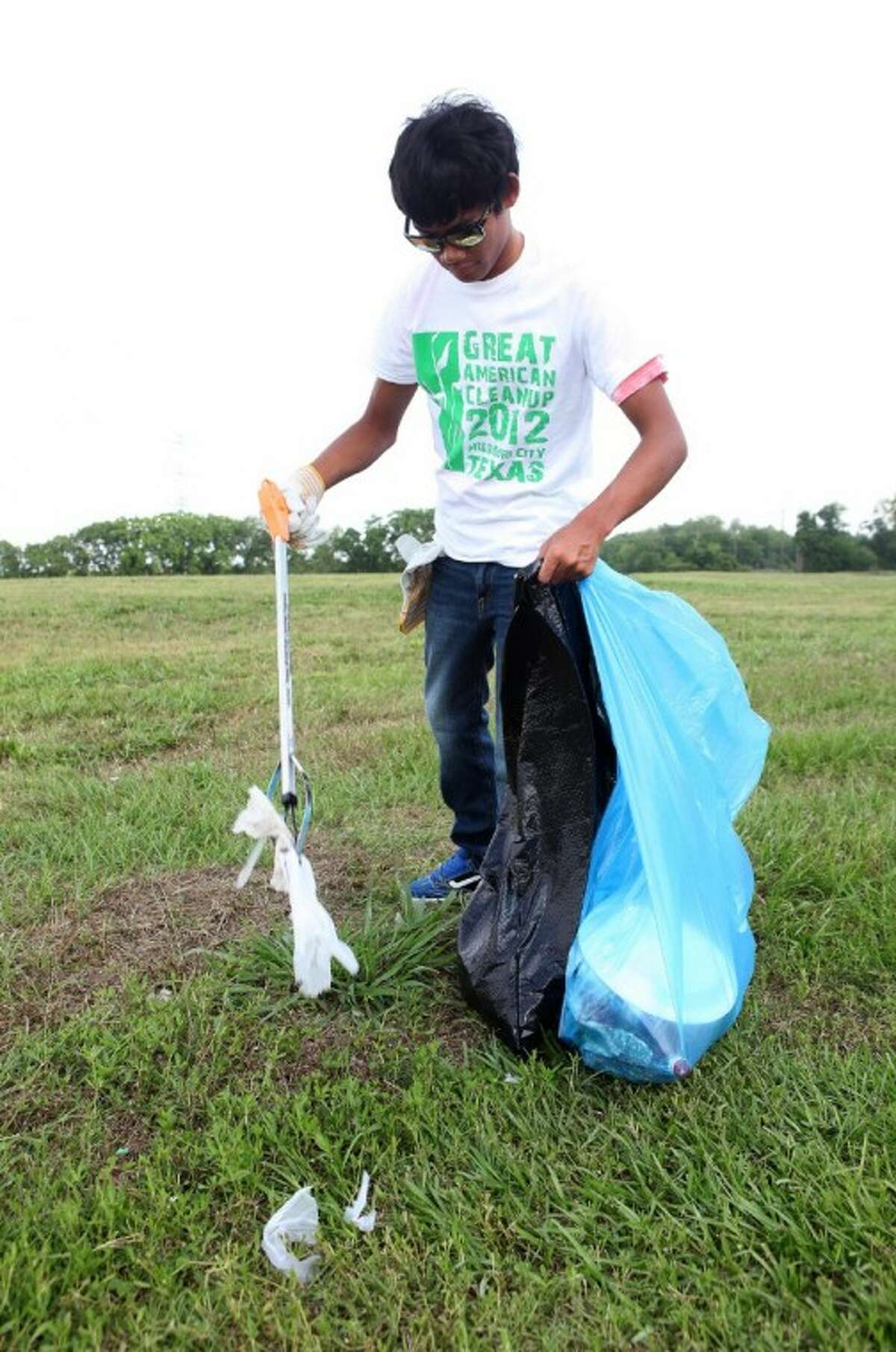 Josh Gicana 16, of Missouri City works in a field picking up trash as part of the Great American Cleanup 2012 at Buffalo Run Park in Missouri City.