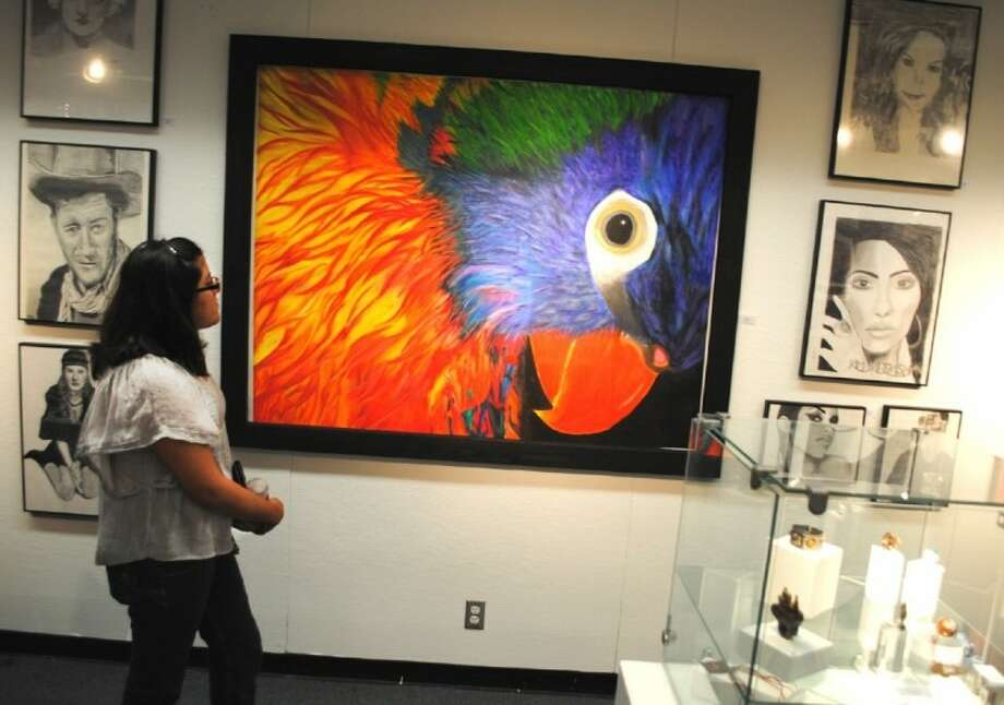 ACC student Nidia Flores, of Manvel, looks at a mural during the spring Student Art Show which will be on display until April 30 at the Fine Arts Gallery. Photo: ACC