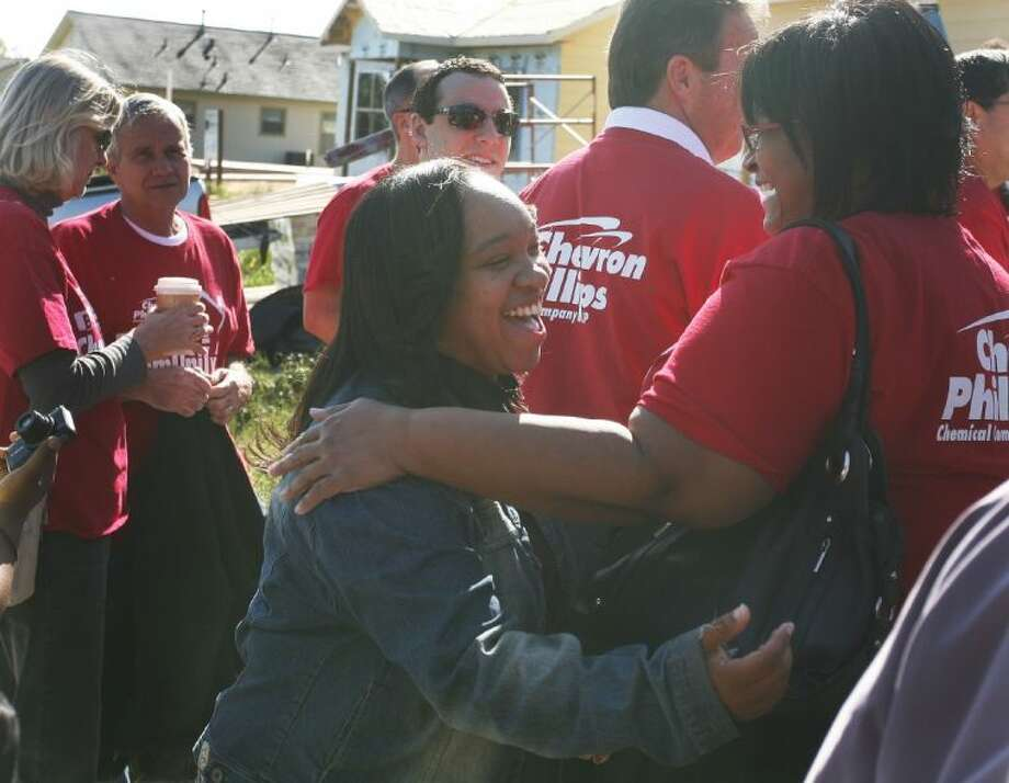 Homeowner Delvina Davis embraces Chevron Phillips Chemical volunteer Quanella Fletcher after the dedication ceremony for Davis' new home in the Cedar Creek neighborhood in Conroe. Photo: Staff Photo By Eric Swist