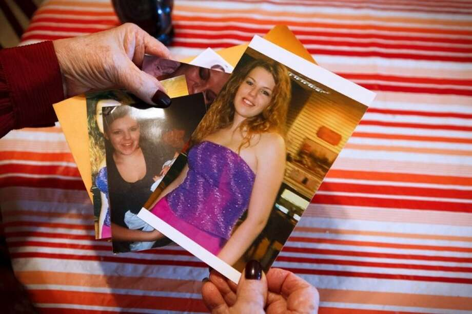 Megan Winfrey's grandmother holds photos of the teen before she was accused of the murder of Coldspring High School janitor Murray Burr. Photo: MICHAEL STRAVATO