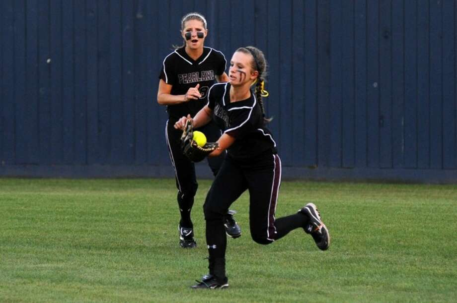 Pearland right fielder Krissa Powell hurries to make a catch while Lady Oiler center fielder Courtney Sams provides back-up help on the play Friday night in a 5-0 playoff win over Fort Bend Austin. Photo: KIRK SIDES