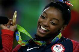 """FILE - In this Aug. 16, 2016, file photo, United States' Simone Biles displays her gold medal for floor during the artistic gymnastics women's apparatus final at the 2016 Summer Olympics in Rio de Janeiro, Brazil. The U.S. Olympic Committee and the sports it oversees are behind the curve when it comes to placing women and minorities in key coaching and leadership positions, according to a set of """"scorecards"""" the federation has compiled over the past three years.  (AP Photo/Rebecca Blackwell, File)"""