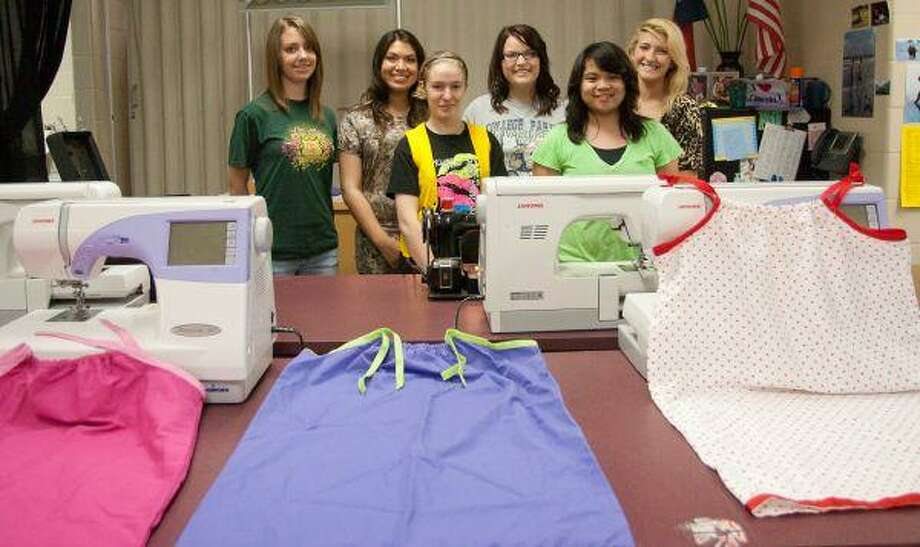 Members of the Students Taking on a Righteous Mission program or the textile and apparel class at College Park High School stand for a group photo next to dresses the group made out of pillowcases for Hope 4 Kids International. / The Courier