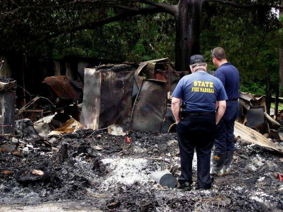 San Jacinto County Fire Marshall James Rogers, right, and State Fire Marshall Jay Evans inspect the remains of Milton Little's residence on FM 223 near Chris Lane in Shepherd. An early morning fire on Monday, April 30, claimed the life of the 101-year-old, World War II veteran.