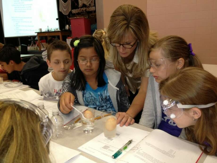 Lyon Elementary fifth-grade science teacher, Vivian Rogers, assists students with experiments during a two-week science camp held on campus.
