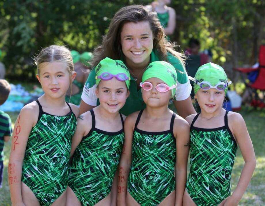 Coach Adair Reidy congratulates the winning 6 & under 100-meter freestyle relay team of Elise Johnson, Jane Johnston, Elizabeth Sullo and Lauren Pearson. Photo: Submitted Photo