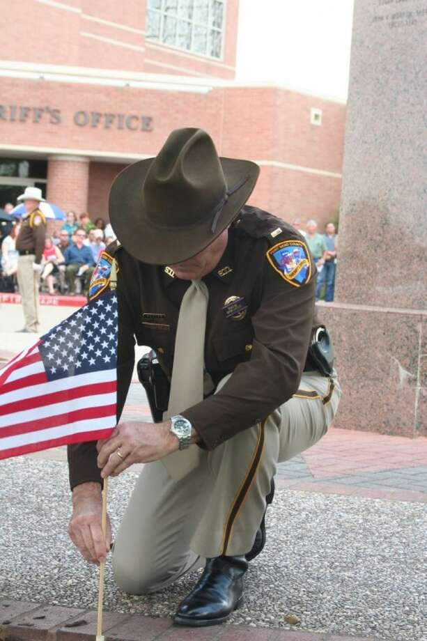 A Fort Bend County Sheriff's Office Deputy places a flag at the 2011 Peace Officers Memorial Service.