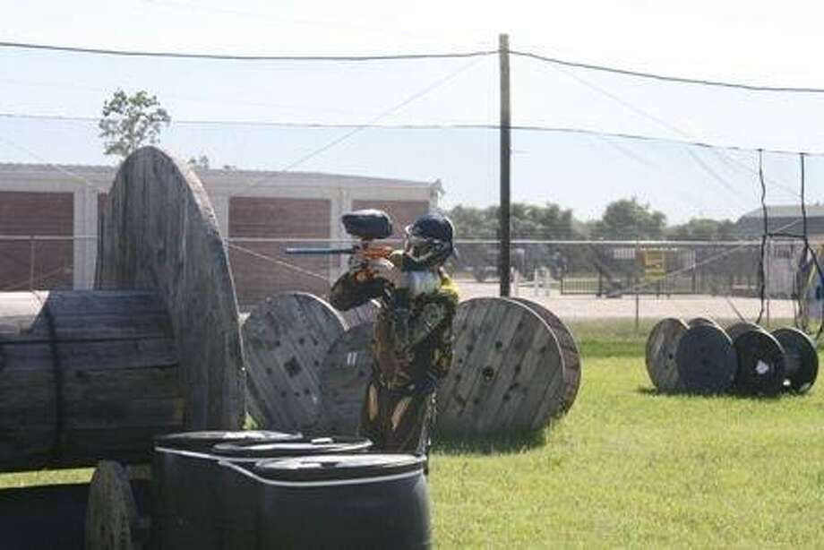 A paint ball player at American Spirit Paintball finds cover behind obstacles so his opponent doesn't shoot him.