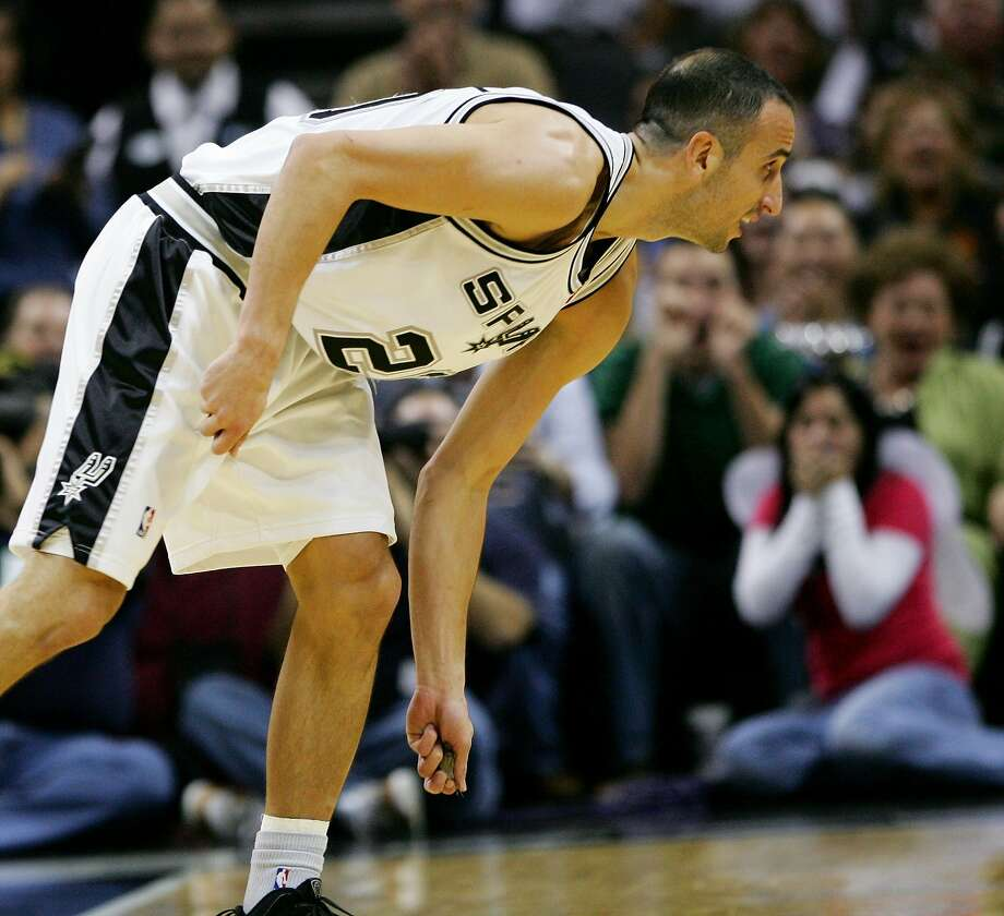 San Antonio Spurs guard Manu Ginobili picks up a bat to remove it from the court after swatting the animal from the air as it flew around the AT&T Center during the first half of an NBA basketball game against the Sacramento Kings, Saturday, Oct. 31, 2009, in San Antonio. (AP Photo/Darren Abate) Photo: Darren Abate, AP