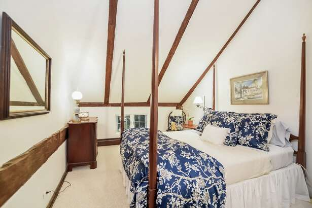 Secondary bedroom: one of the second floor bedrooms has hand-hewn exposed beams on the walls and ceiling, a reminder of the home's origins as a barn.