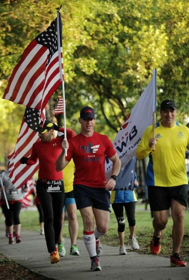 Members of the Team RWB led the pack of runners carrying the American Flag during the Run for Boston tribute run in Kingwood April 20, 2013.