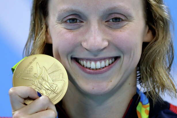 "FILE - In this Aug. 12, 2016, file photo, United States' Katie Ledecky shows off her gold medal in the women's 800-meter freestyle medals ceremony during the swimming competitions at the 2016 Summer Olympics in Rio de Janeiro, Brazil. A bill moving forward in Congress would block the IRS from taxing most medals or other prizes awarded to U.S. Olympians. The U.S. Olympic Committee awards cash prizes to Olympic medal winners: $25,000 for gold, $15,000 for silver and $10,000 for bronze. Because the money is considered earned income, it is taxed — a practice some lawmakers refer to the ""victory tax."" (AP Photo/Michael Sohn)"