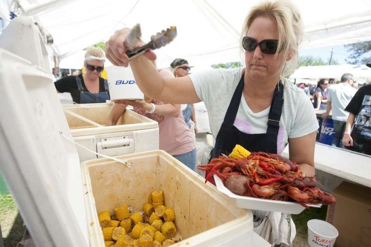 Ann Logan with Lonestar Catering loads up a tray of boiled crawfish during a previous Texas Crawfish and Music Festival Sunday in Old Town Spring. This year's event is weekends April 25 through May 4.