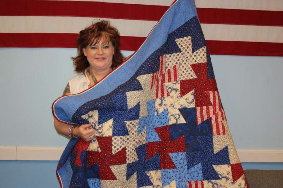 "Bridgette Stein displayed a Quilt of Valor that will be presented to a veteran. She explained, ""If you can sew a straight line, you can quilt."" Stein hopes more volunteers will participate in making these special quilts by the May 3 deadline."