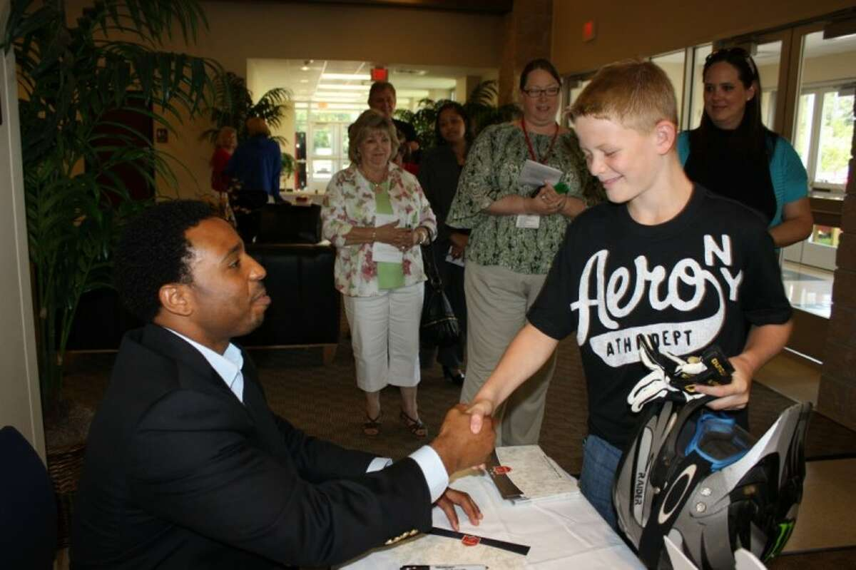 Former Houston Texan J.J. Moses, left, congratulates Riley Hulsey, right, on winning a gift basket at the Greater Cleveland Chamber of Commerce luncheon on July 7. Moses signed autographs for fans after the event.