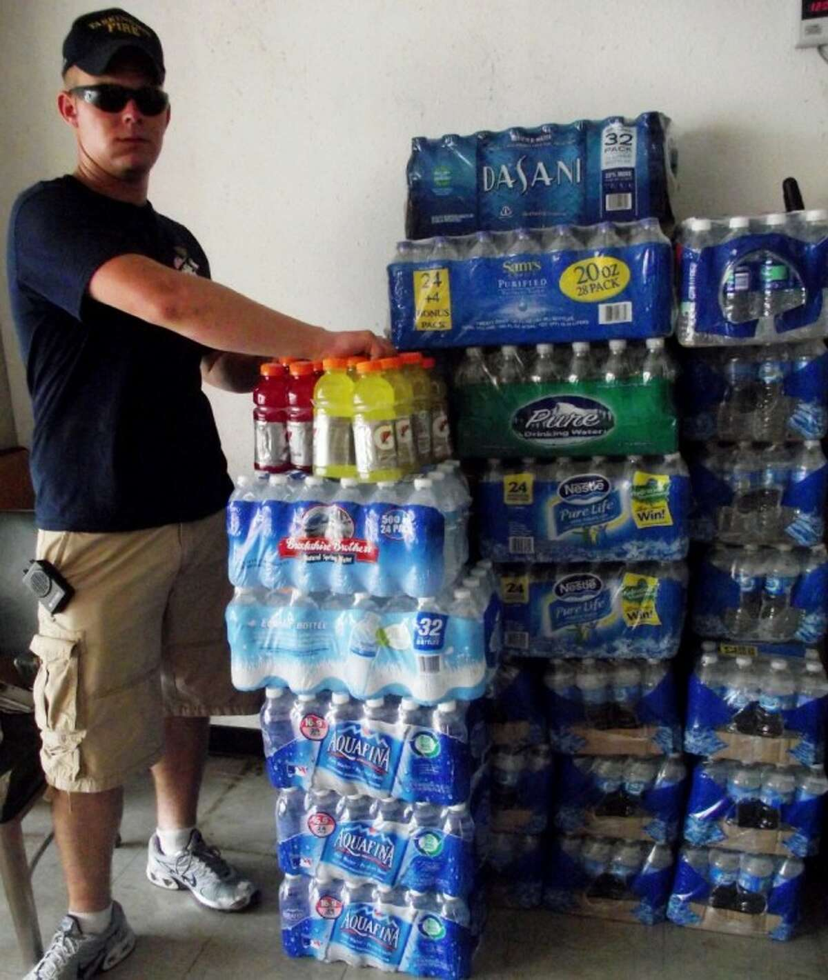 Tarkington VFD Captain Ben Burnett adds to the stacks of water and Gatorade donated to the fire station on Saturday. Liberty County fire departments held a county-wide water/Gatorade drive on July 9 to help offset costs of keeping firefighters hydrated at fire scenes.
