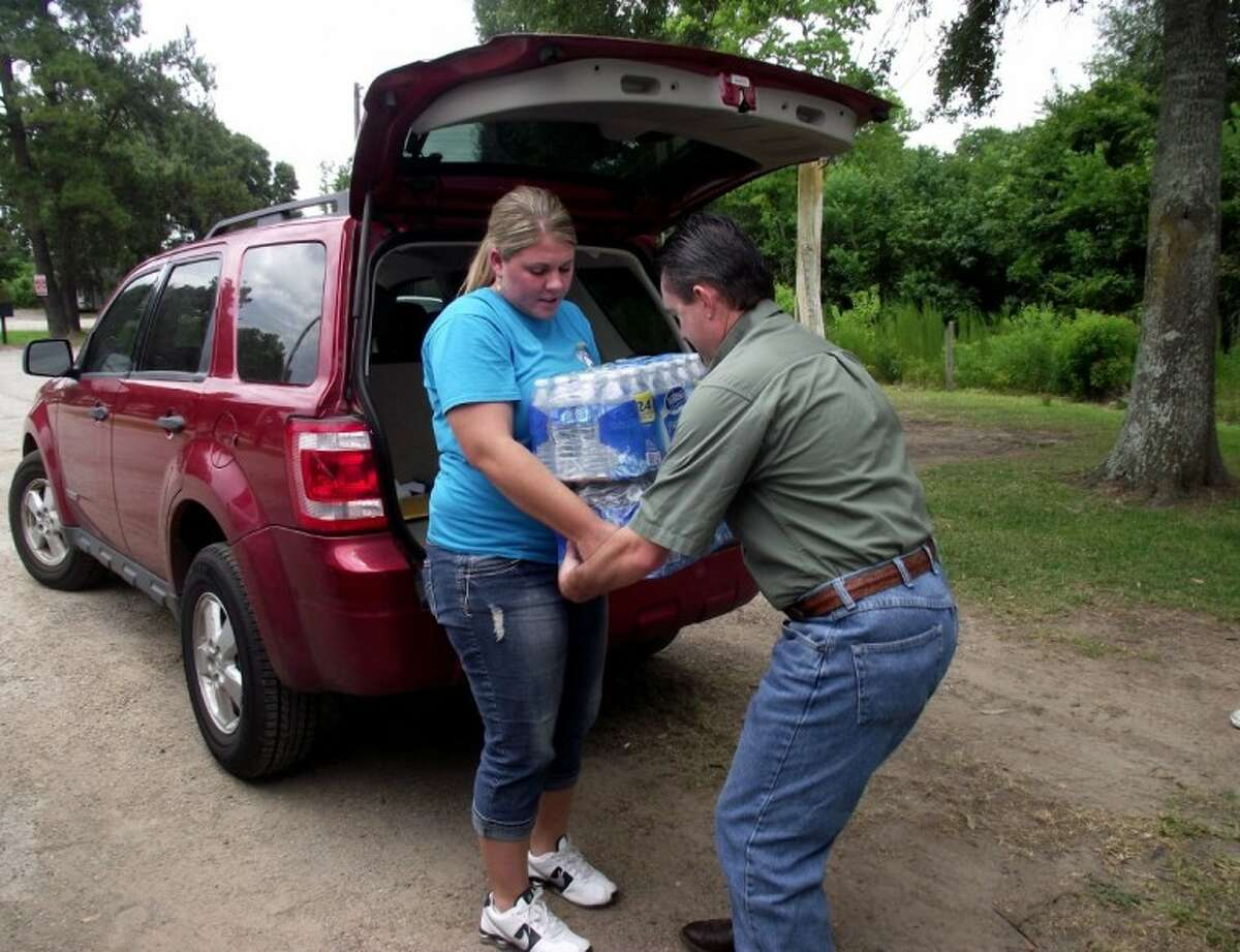 TVFD Firefighter Kirsten Corley gets a helping hand from Harris County Sheriff's Captain James Dousay who donated several cases of water to the fire department on Saturday. Dousay was seriously injured last year when he was gored by a bull, and credits his survival to the help he received from first responders and EMTs on the scene.