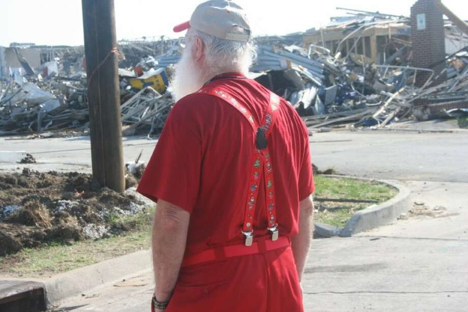 "Houston-based professional Santa Glenn Westberry surveys the tornado damage in the ""war zone"" of Joplin, Mo. during the Lone Star Santas ""convoy of toys"" trip. (Submitted photo)"