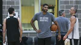 Tim Duncan enjoys the company of his old teammate Manu Ginobili as the Spurs practice on Sept. 28, 2016.
