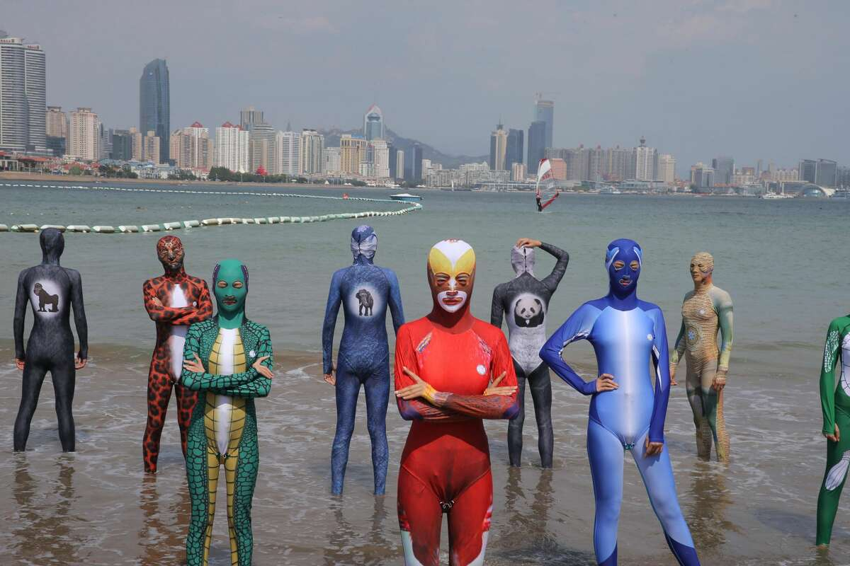 Women and men wearing siamesed facekinis pose on beach on August 28, 2016 in Qingdao, Shandong Province of China. Facekini has been China\'s popular beach trend and the latest siamesed facekini designed with various patterns like dragon, phoenix and peacock and many others catered to women and men\'s pleasure. Different from the old facekini protecting head only, the siamesed facekini kept your head and upper body away from sunshine.