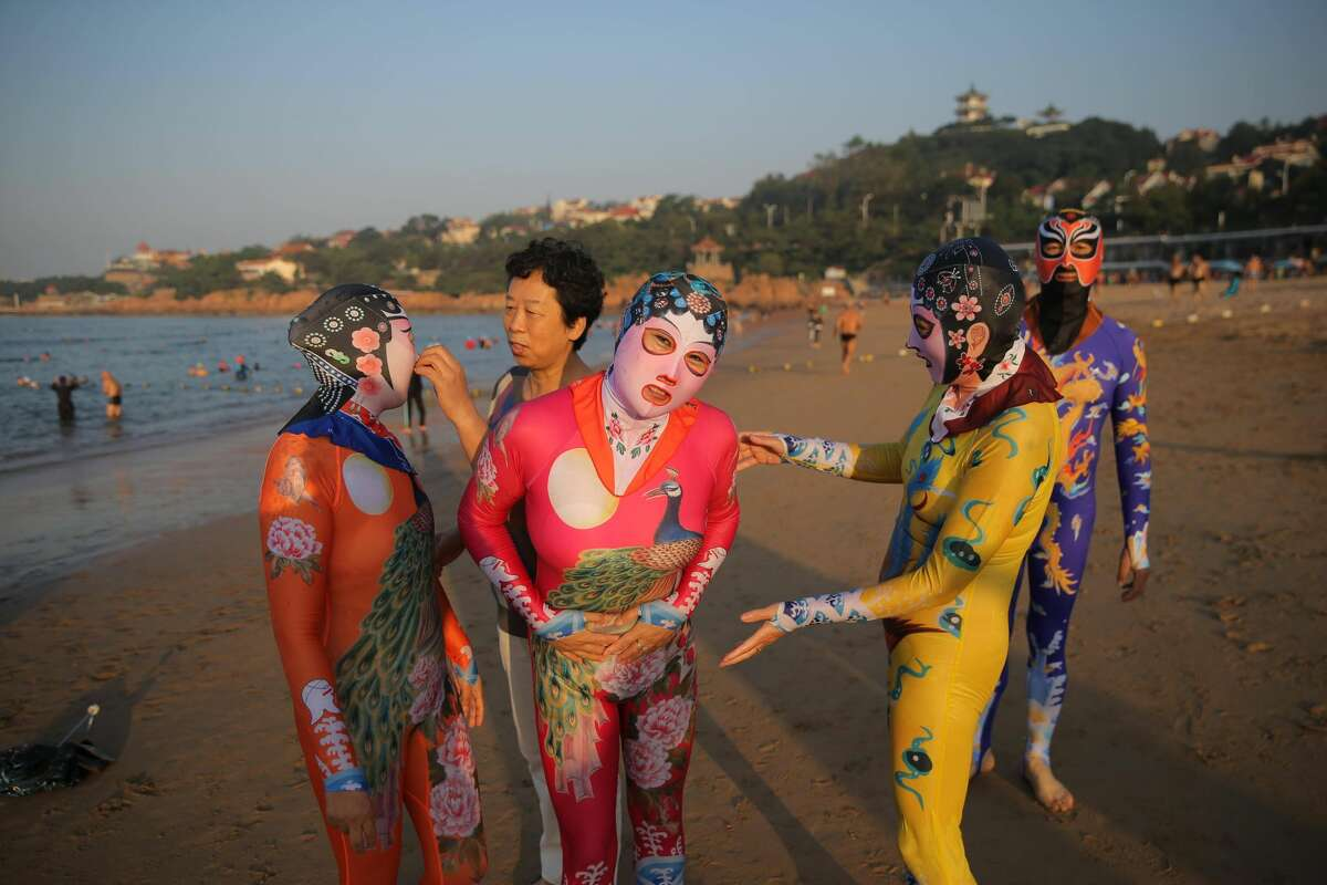 Zhang Shifan (L2), inventor of facekini adjusts siamesed facekini for a woman on August 29, 2016 in Qingdao, Shandong Province of China. Facekini has been China\'s popular beach trend and the latest siamesed facekini designed with various patterns like dragon, phoenix and peacock and many others catered to women and men\'s pleasure. Different from the old facekini protecting head only, the siamesed facekini kept your head and upper body away from sunshine.