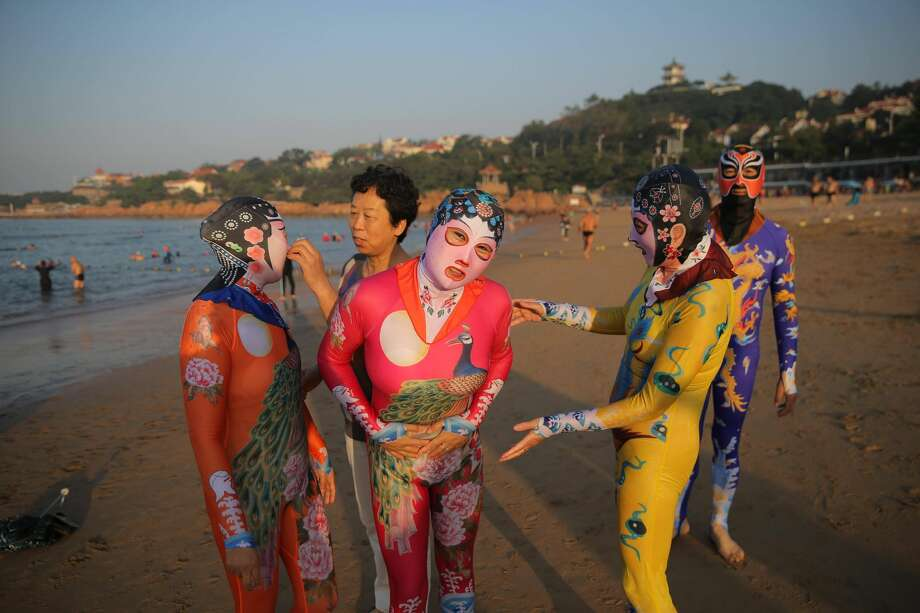 Zhang Shifan (L2), inventor of facekini adjusts siamesed facekini for a woman on August 29, 2016 in Qingdao, Shandong Province of China. Facekini has been China\'s popular beach trend and the latest siamesed facekini designed with various patterns like dragon, phoenix and peacock and many others catered to women and men\'s pleasure. Different from the old facekini protecting head only, the siamesed facekini kept your head and upper body away from sunshine. Photo: VCG/VCG Via Getty Images