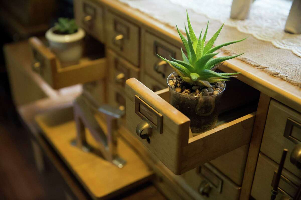 The an old wooden library card catalog case in Janie and Jason Norris' home. Three open drawers hold succulents in pots. On top she arranged, among other things, a silver sugar and creamer, a couple of Willow Tree angels and a photograph in a vintage metal frame and holder found at, naturally, a thrift store.